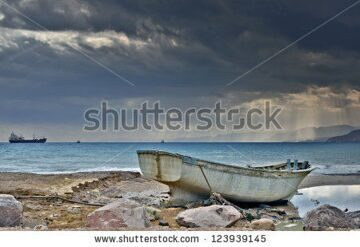 stock-photo-old-fishing-boat-on-marine-beach-after-tropical-storm-123939145