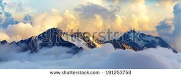 stock-photo-alpine-landscape-with-peaks-covered-by-snow-and-clouds-banner-panorama-191253758