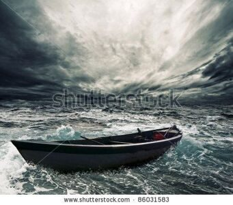 stock-photo-abandoned-boat-in-stormy-sea-86031583