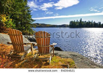 stock-photo-adirondack-chairs-at-shore-of-lake-of-two-rivers-ontario-canada-84094621