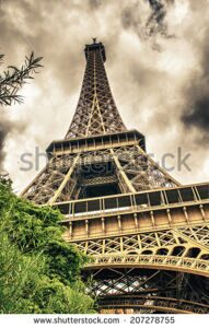 stock-photo-paris-eiffel-tower-with-summer-trees-on-a-cloudy-sky-207278755
