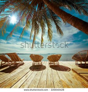 stock-photo-amazing-tropical-beach-landscape-with-palm-tree-and-chairs-for-relaxation-on-wooden-terrace-travel-220040428