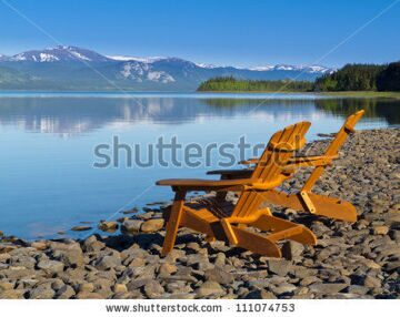 stock-photo-two-empty-wooden-adirondack-chairs-or-muskoka-deckchairs-on-stony-shore-overlooking-scenic-calm-111074753