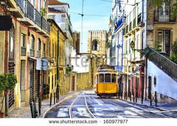 stock-photo-romantic-lisbon-street-with-the-typical-yellow-tram-and-lisbon-cathedral-on-the-background-160977977